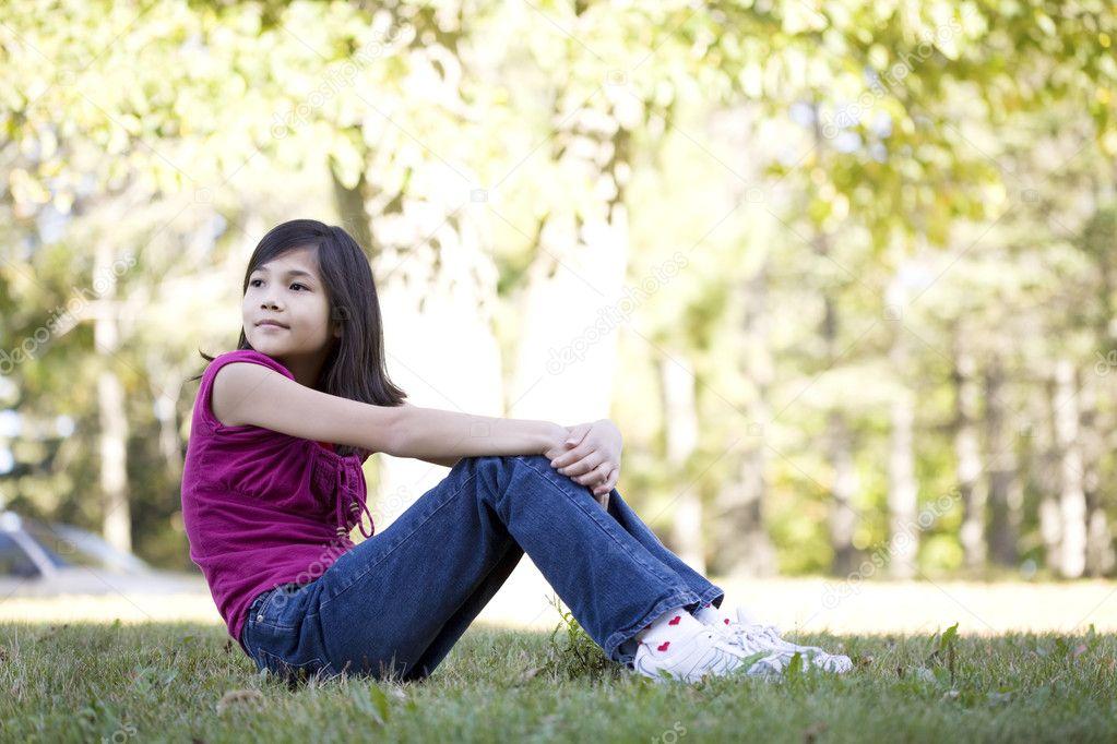 Little girl sitting on grass