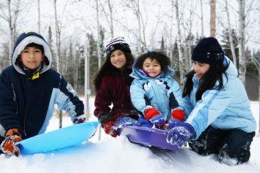 Four kids enjoying winter outdoors sledding stock vector