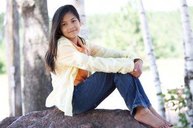 Little girl sitting under trees