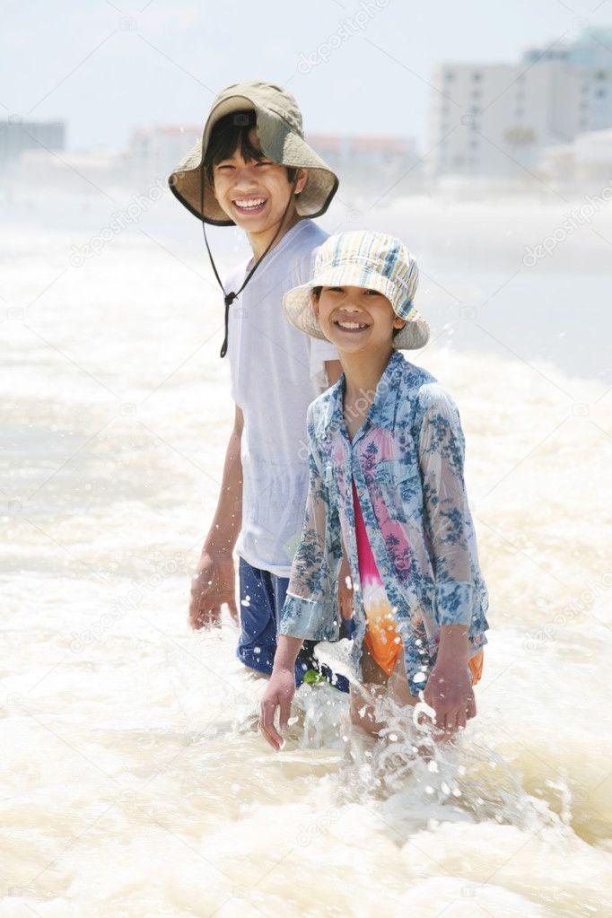 Children knee deep in ocean waves