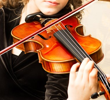 Young woman practicing her violin