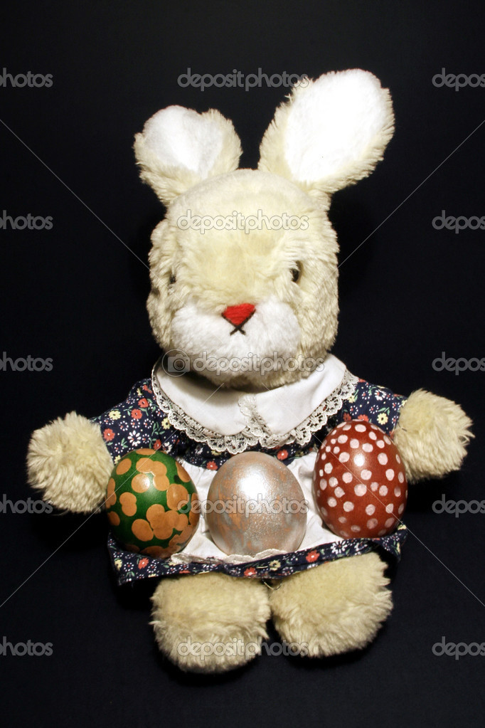 Bunny toy with three easter eggs on black background stock vector