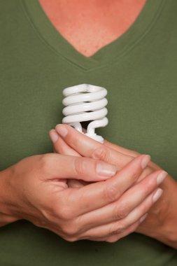 Female Hands Holding Energy Saving Bulb