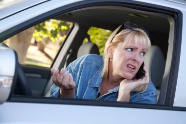 Concerned Woman Using Cell Phone in Car