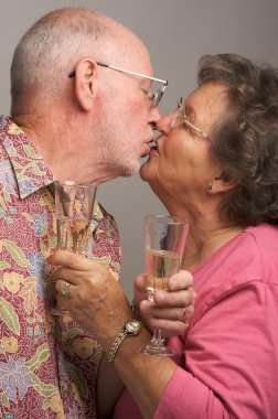 Senior Couple with Champagne Kissing