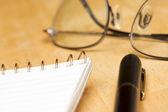 Fényképek toll, pad és szemüveg fa háttér