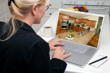 Woman In Kitchen Using Laptop with Kitchen Interior on Screen