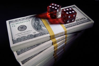 Stacks of Money and Red Dice on Black