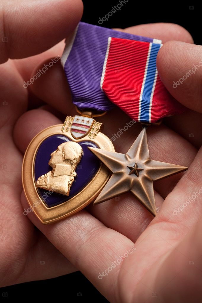 Man Holding Purple Heart and Bronze War Medals in The Palm of His Hand.