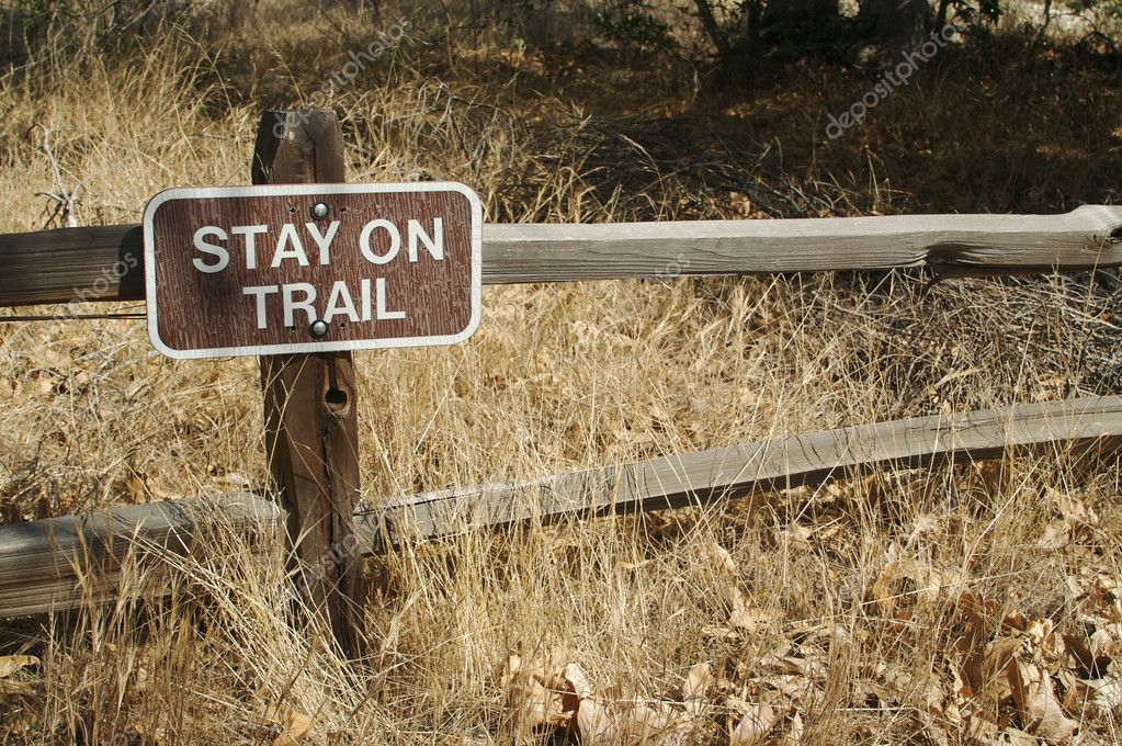 Stay on Trail Sign on Wooden Fence