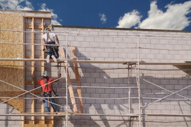 Carpenters Working Diligently on Brick Wall