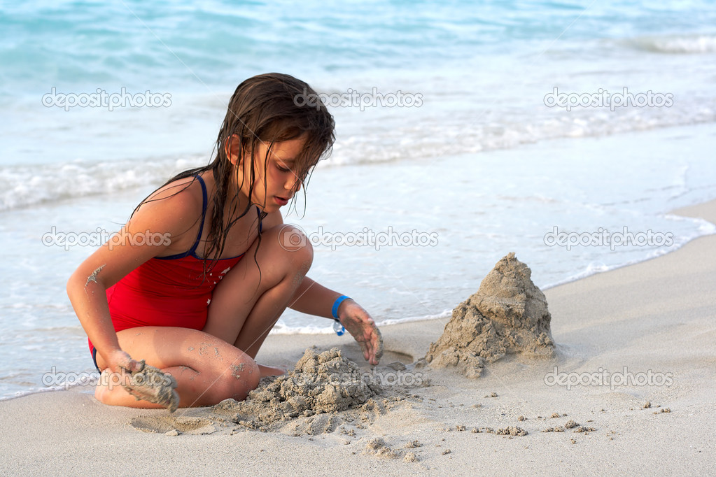 Beautiful latin girl building a sand castle in the bea