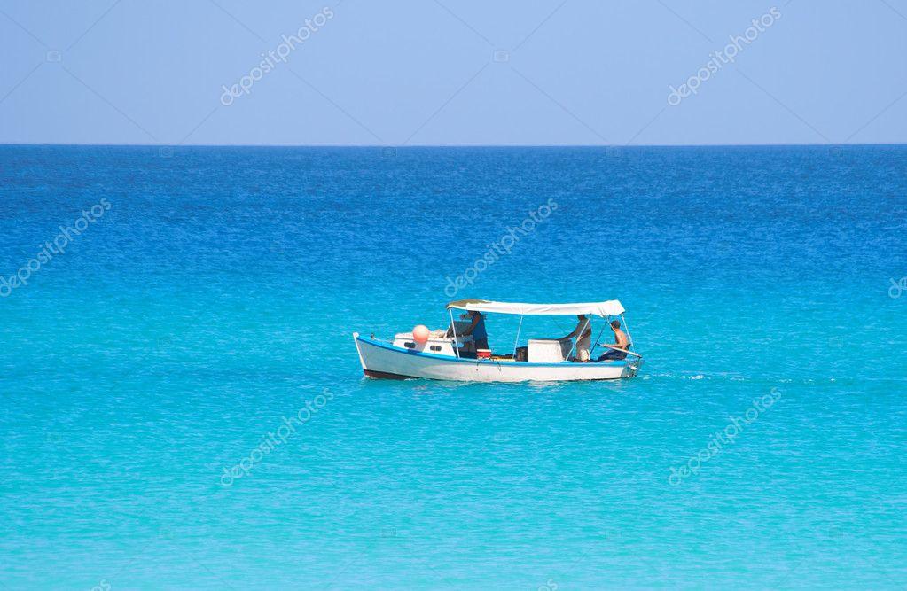 Petit bateau de p che dans une mer calme bleue photo for Dans un petit bateau
