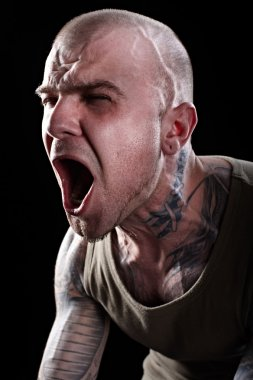 Angry tattooed man screaming