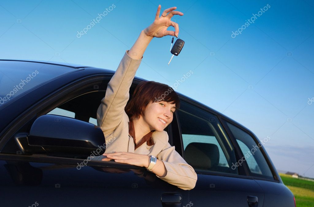 Girl with keys in a car is smiling