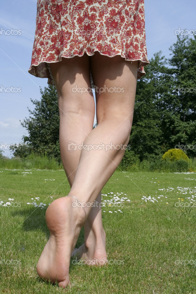 Woman legs relaxing on sunny garden