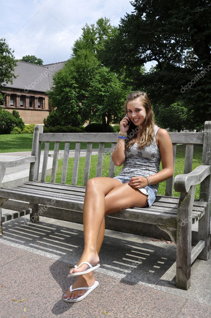 Teenage girl sitting on bench with phone