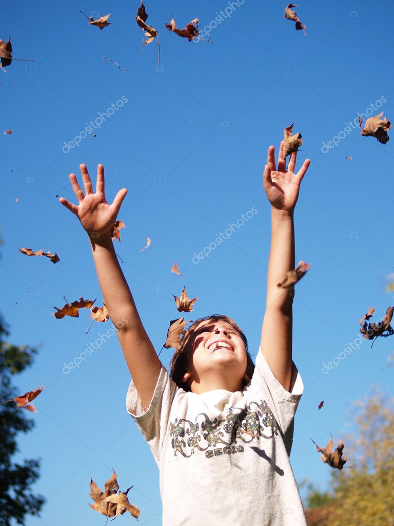 Young boy throwing leaves in the air