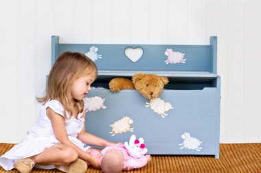 Child Playing by a Toy Box