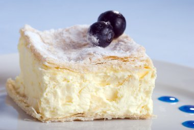 Custard cake square on a plate with blue