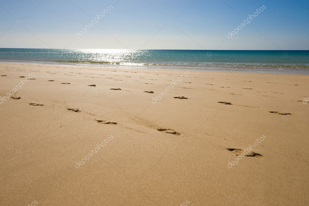 A beach with footsteps in front