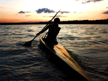 Kayaker against sunset
