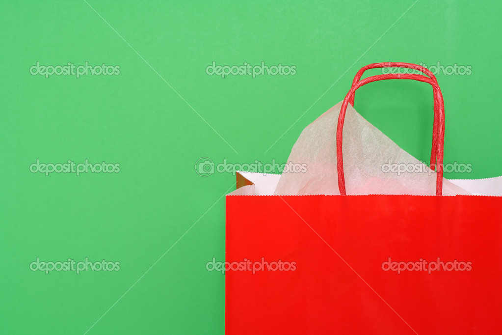 Red shopping bag on green background