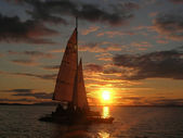 Photo Sailboat at sunset with cloudy sky