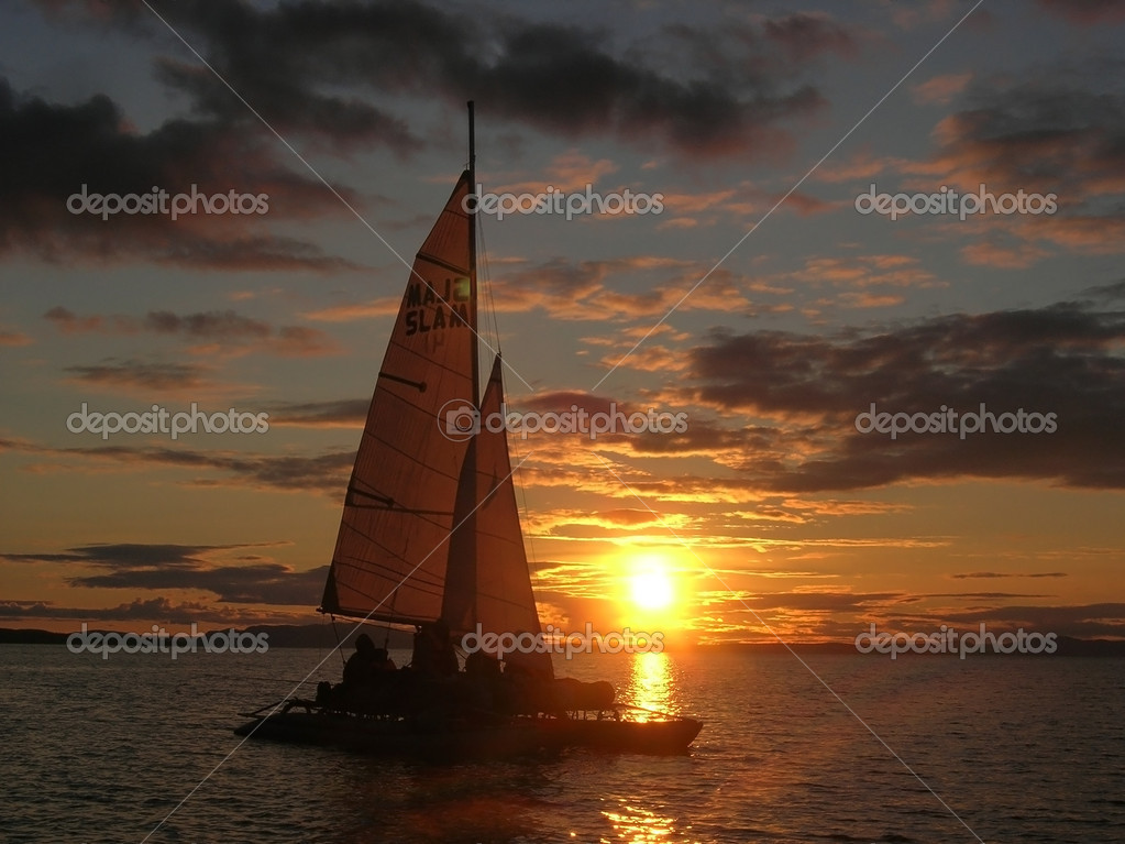 Sailboat at sunset with cloudy sky