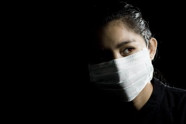 Flu alarm: protective face mask on beautiful asian woman. low-key picture. stock vector