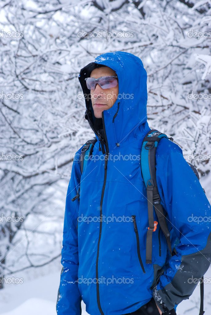 A backpacker man in winter forest