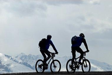 Silhouette two mountain bikers