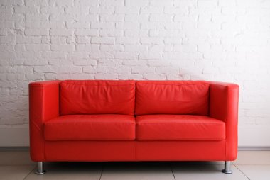 Red sofa and white brick wall stock vector