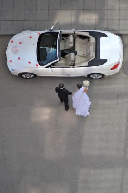 Bride and groom going to car