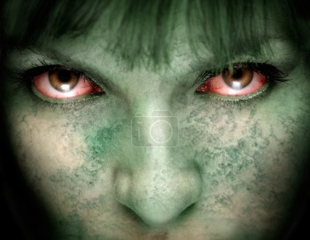 Closeup of female zombie face with bloodshot eyes and green skin