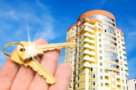 Foto de Concepto inmobiliario. claves de oro en los dedos con edificio - Imagen libre de derechos
