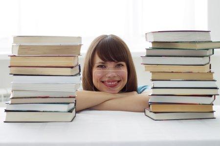 Photo pour Visage de la jeune fille et les deux piles de livres - image libre de droit
