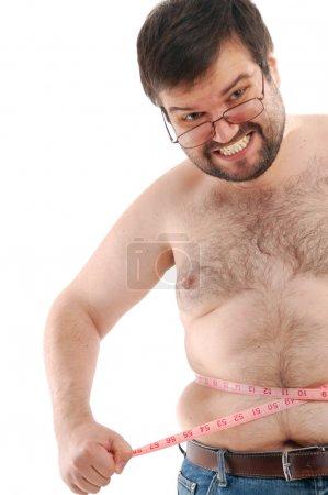 Foto de Hombre grande enojado midiendo su vientre contra el fondo blanco - Imagen libre de derechos