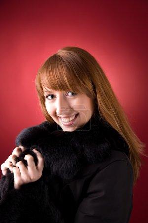 Photo pour Jeune fille souriante en manteau de fourrure sur fond rouge - image libre de droit
