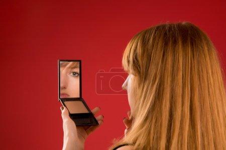 Beautiful girl looking in mirror