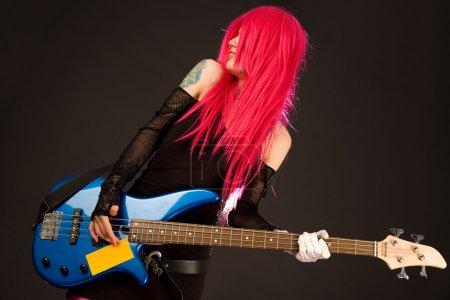 Photo pour Fille de rock souriant en tenue de fou avec la guitare basse - image libre de droit