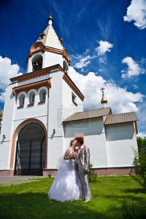 Newly married kiss on the church