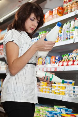 The girl the buyer in shop chooses milk