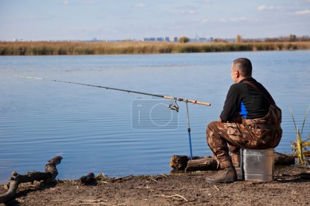 Sitting fisherman with a fishing tackle