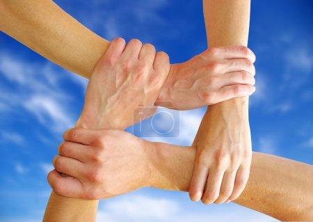 Photo pour Mains liées sur un fond de ciel symbolisant le travail d'équipe et l'amitié - image libre de droit