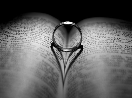 Photo for Wedding Ring and heart shaped shadow over a Bible - Royalty Free Image
