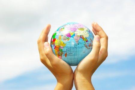Photo pour Main tient un globe sur un ciel - image libre de droit
