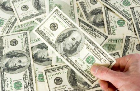 Hand holding 100 dollar on dollar background...