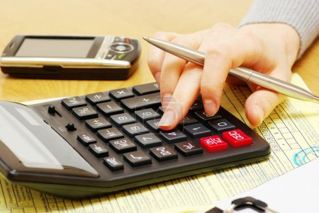 Photo pour Fermeture d'une jeune femme calculant des factures - image libre de droit