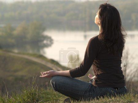 Photo pour Jeune femme méditant sur le dessus à l'extérieur de colline - image libre de droit